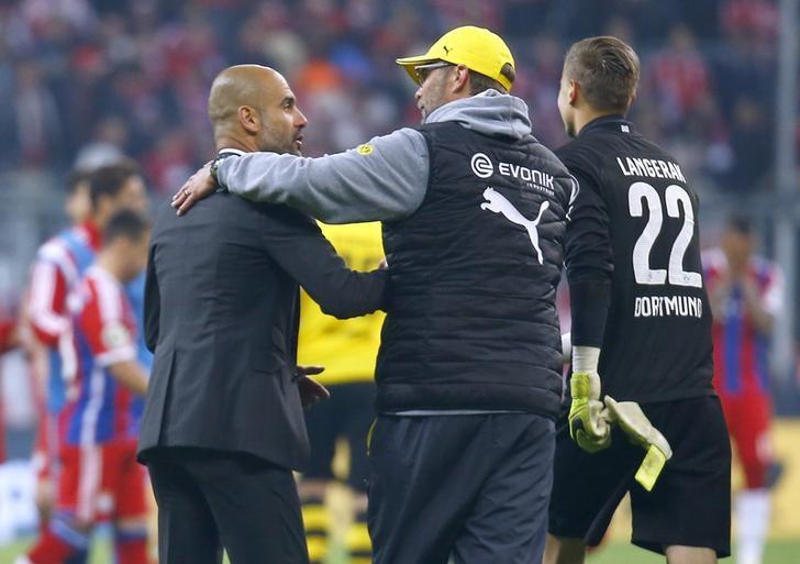 Bayern Munich's coach Pep Guardiola (L) congratulates Borussia Dortmund's coach Juergen Klopp (C) on winning the German Cup (DFB Pokal) semi-final soccer match in Munich, Germany April 28, 2015. Dortmund won the match 2-0 on penalties.             REUTERS/Kai Pfaffenbach/File Photo