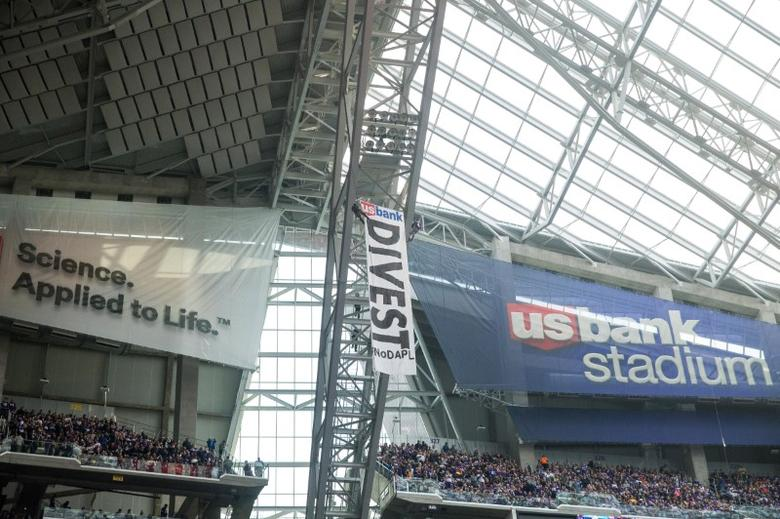 Jan 1, 2017; Minneapolis, MN, USA; Two protestors rappel from the rafters with a banner against the Dakota Pipeline  during the second quarter during a game between the Minnesota Vikings and Chicago Bears at U.S. Bank Stadium. Brace Hemmelgarn-USA TODAY Sports