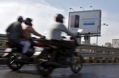 Men ride on motorbikes past an Apple iPhone SE advertisement billboard in Mumbai, India, April 26, 2016.  REUTERS/Shailesh Andrade