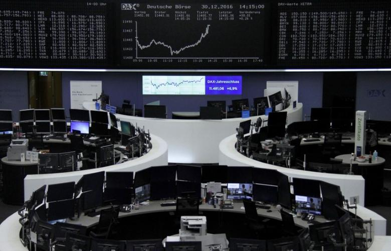 Traders work at their desks in front of the German share price index, DAX board, at the stock exchange in Frankfurt, Germany, December 30, 2016.      REUTERS/Staff/Remote