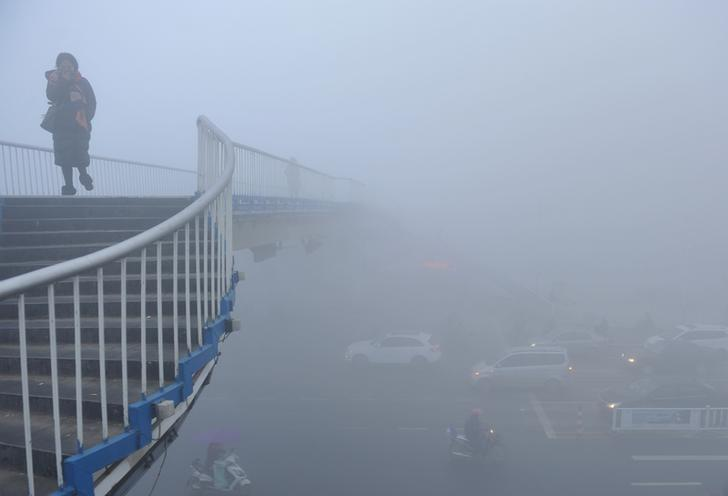 A woman walks past a bridge among heavy smog during a polluted day in Fuyang, Anhui province, China, January 3, 2017. China Daily/via REUTERS