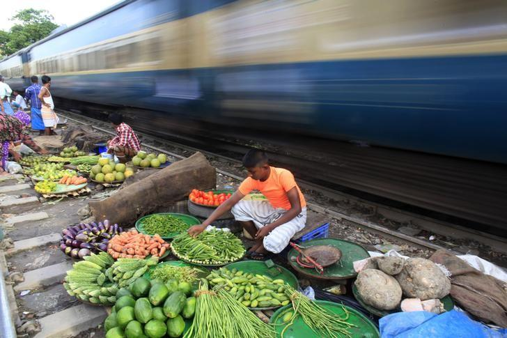 A vendor sorts vegetables next to a railway track as a train passes by, in Dhaka September 10, 2012. REUTERS/Andrew Biraj/Files