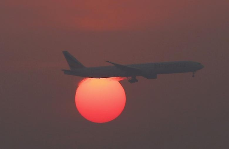 A plane flies over the setting sun in the sky at Beijing International Airport, China, March 2, 2016.  REUTERS/Kim Kyung-Hoon/File Photo - RTX2RA0J