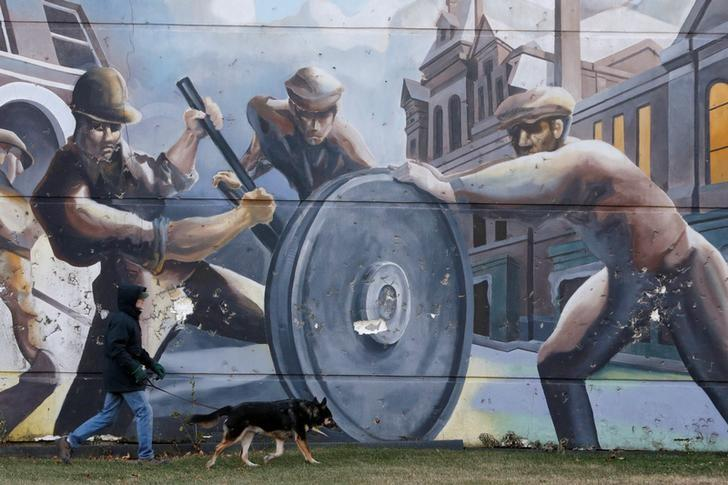 A man walks his dog past a mural depicting factory workers in the historic Pullman neighborhood in Chicago November 20, 2014. REUTERS/Andrew Nelles/File Photo