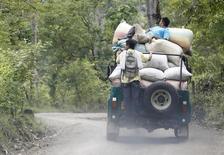 Campesinos llevan café en un jeep en un camino cerca de Gaitania en el departmento de Tolima en Colombia. 3 de mayo de 2014. Colombia produjo 14,23 millones de sacos de 60 kilos de café durante el 2016, en línea con lo esperado, el mayor resultado de los últimos 23 años, que se apoyó en un programa de renovación de cultivos, informó el martes la Federación Nacional de Cafeteros. REUTERS/Jaime Saldarriaga