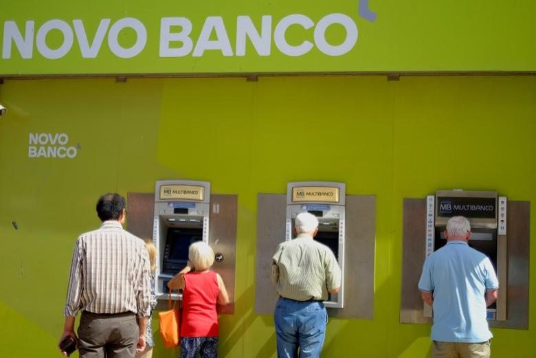 People use ATM machines outside a branch of Novo Banco in Lisbon, Portugal, September 26, 2016. REUTERS/Phil Noble