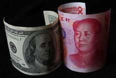 En la imagen, un billete de 100 yuanes junto a un billete de 100 dólares, tomada en Beijing, China. 7 de noviembre 2010. China intervino el miércoles por segundo día en los mercados cambiarios del yuan a nivel local y en el exterior, lo que generó especulaciones respecto a que busca reforzar el control sobre su divisa antes de que Donald Trump asuma su mandato como presidente de Estados Unidos el 20 de enero. REUTERS/Petar Kujundzic