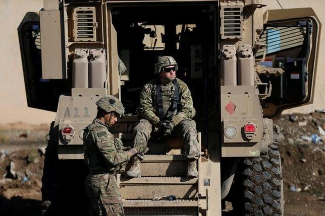US army soldiers sit next a military vehicle in the town of Bartella, east of Mosul, Iraq, December 27, 2016. REUTERS/Ammar Awad
