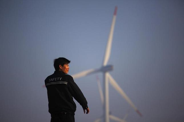 A security guard stands in front of windmills used to generate energy in Shanghai November 28, 2011.  REUTERS/Aly Song