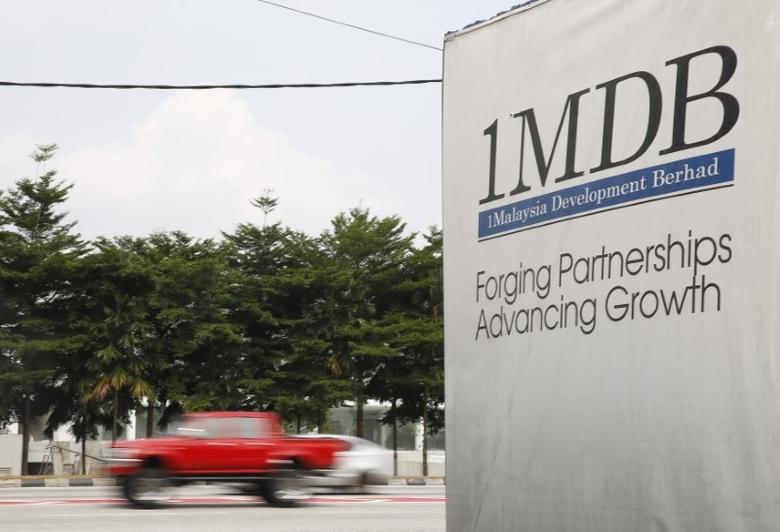 Traffic passes a 1Malaysia Development Berhad (1MDB) billboard at the Tun Razak Exchange development in Kuala Lumpur, Malaysia, July 6, 2015.  REUTERS/Olivia Harris