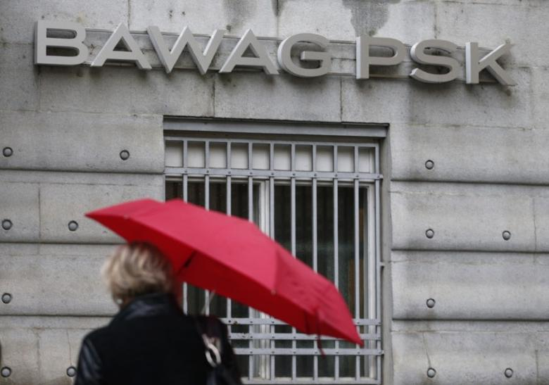 A woman holding an umbrella passes the headquarters of Austrian lender BAWAG PSK in Vienna, Austria, February 29, 2016. REUTERS/Heinz-Peter Bader