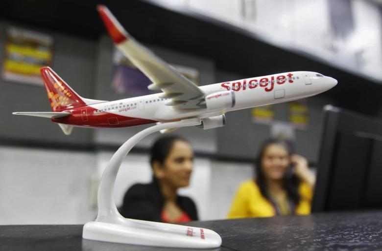 Employees work inside a travel agency office besides a model of a SpiceJet aircraft in the western Indian city of Ahmedabad February 14, 2014.  REUTERS/Amit Dave