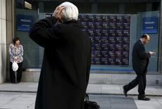 Un hombre mira un tablero electrónico que muestra información de la bolsa de Japón fuera de una correduría en Tokio, Japón. 2 de marzo 2016. Las bolsas de Asia rebotaban el viernes a máximos en cuatro semanas luego de que un repunte del dólar provocado por la elección de Donald Trump para la presidencia de Estados Unidos perdió impulso. REUTERS/Thomas Peter - RTS8VY3