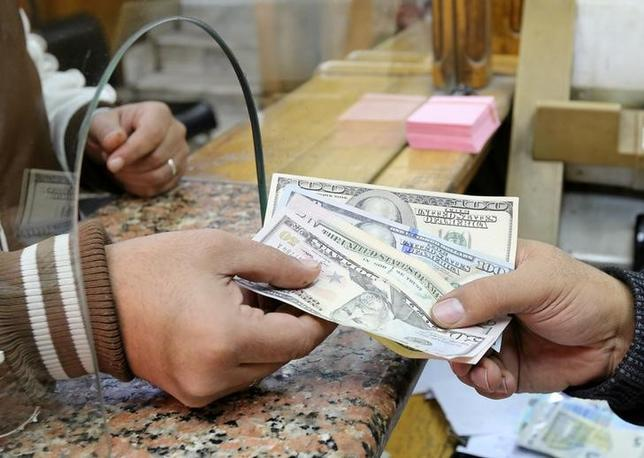 A customer exchanges U.S. dollars to Egyptian pounds in a foreign exchange office in central Cairo, Egypt December 27, 2016. REUTERS/Mohamed Abd El Ghany - RTX2WLMR