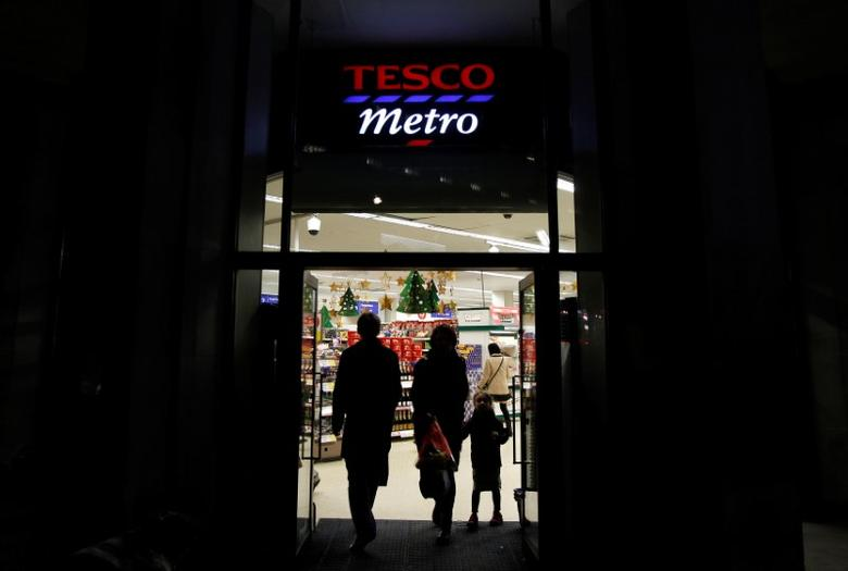 Customers enter and exit a Tesco shop in London, Britain, December 8, 2011.    REUTERS/Suzanne Plunkett/File Photo