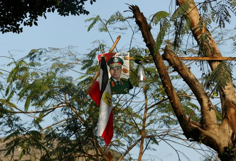 A poster of Egyptian President Abdel Fattah al-Sisi which reads ''We will die and Egypt will live'' and the national flag are seen on a tree at the center of downtown in Cairo, Egypt December 26, 2016. REUTERS/Amr Abdallah Dalsh - RTX2WHPO