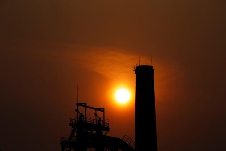 The sun sets behind a chimney of a steel mill in Tangshan, Hebei province February 18, 2014. REUTERS/Petar Kujundzic/File Photo