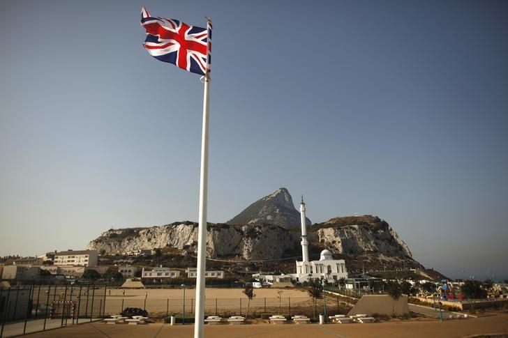 A Union flag flies at Europa Point in front of the Rock (rear), a monolithic limestone promontory, and the Ibrahim-al-Ibrahim mosque in Gibraltar, south of Spain August 12, 2013.  REUTERS/Jon Nazca/Files