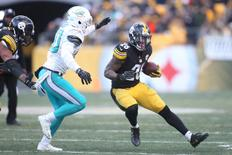 Jan 8, 2017; Pittsburgh, PA, USA; Pittsburgh Steelers running back Le'Veon Bell (26) carries the ball as Miami Dolphins free safety Bacarri Rambo (30) chases during the second half in the AFC Wild Card playoff football game at Heinz Field. Mandatory Credit: Charles LeClaire-USA TODAY Sports