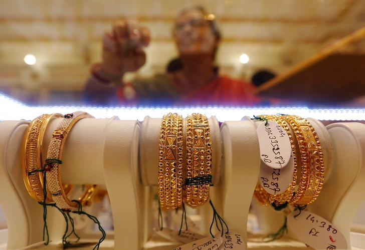 Gold bangles are on display as a woman makes choices at a jewellery showroom during Dhanteras, a Hindu festival associated with Lakshmi, the goddess of wealth, in Kolkata, October 28, 2016. REUTERS/Rupak De Chowdhuri/Files