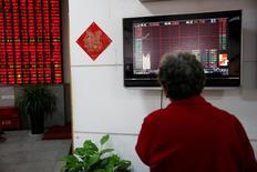 Инвестор смотрит на табло с информацией о торгах в брокерской компании Шанхая. Фондовые индексы Китая успешно начали неделю благодаря оборонным акциям, в то время как госпредприятия обдумывали планы реформ смешанной формы собственности.  REUTERS/Aly Song