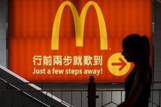 McDonald's Corp ha llegado a un acuerdo para vender una participación mayoritaria en sus negocios de China y Hong Kong al conglomerado respaldado por el estado CITIC Ltd y a Carlyle Group LP por un máximo de 2.100 millones de dólares. En esta imagen de archivo, una mujer pasa frente a un local de McDonald's en Hong Kong el 25 de julio de 2014.  REUTERS/Tyrone Siu/Files Photo