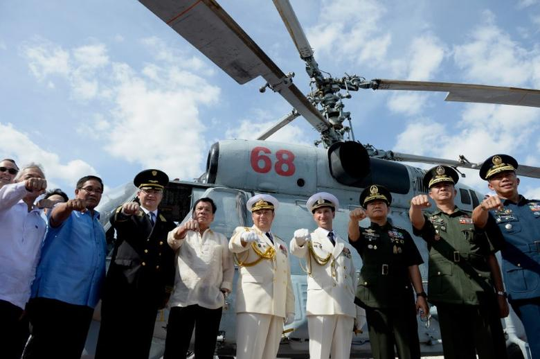 Philippine President Rodrigo Duterte (4th L) gestures with Russian Ambassador to the Philippines Igor Khovaev (3rd L), Russia's Rear Admiral Eduard Mikhailov (5th L), and other Philippine and Russian officials in front of the Ka-26 anti-submarine helicopter at the anti-submarine navy ship Admiral Tributs at the south pier in Metro Manila, Philippines January 6, 2017. REUTERS/Noel Celis/Pool