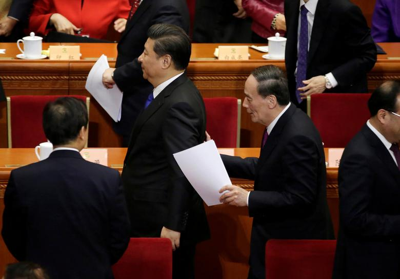 China's Politburo Standing Committee member Wang Qishan (C, R), the head of China's anti-corruption watchdog, talks to President Xi Jinping (C, L) at the Great Hall of the People in Beijing, China, March 3, 2016. REUTERS/Jason Lee/File Photo