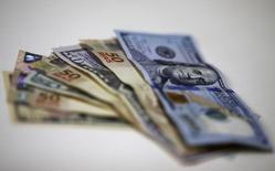 Imagen de archivo. Billetes de dólar y de real brasileño, casa de cambio en Río de Janeiro, 10 sep, 2015. Los operadores de monedas latinoamericanas observarán esta semana al Banco Central de Brasil (BCB), que aplicaría un recorte de tasas de interés sólido en su primer encuentro monetario del año, al tiempo que México estará pendiente de los datos de inflación de diciembre. REUTERS/Ricardo Moraes/Imagen de archivo