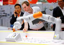 FILE PHOTO: A Kuka technician programs a robot arm of German industrial robot maker Kuka at the company's stand during the Hannover Fair in Hanover, Germany April 25, 2016. REUTERS/Wolfgang Rattay/File Photo