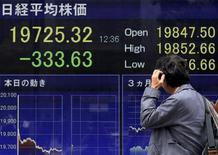 Una persona observando un monitor con información bursátil en una correduría en Tokio, abr 30, 2015. Las bolsas de Asia recortaban unas ganancias iniciales el lunes medio de la cautela de los inversores antes de una conferencia de prensa que el presidente electo de Estados Unidos, Donald Trump, ofrecerá el miércoles, donde sus opiniones sobre el comercio mundial y China serán examinadas cuidadosamente.  REUTERS/Yuya Shino