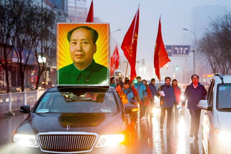 A picture of China's late Chairman Mao Zedong is seen on top of car as people gather to celebrate Mao's 123rd birth anniversary in Shaoshan, Hunan province, December 26, 2016. REUTERS/Stringer