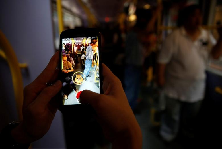 A passenger plays the augmented reality mobile game ''Pokemon Go'' by Nintendo inside a bus in Hong Kong, China August 12, 2016. REUTERS/Tyrone Siu