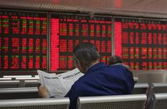 """China prevé consolidar cinco empresas audiovisuales y de comunicación de propiedad estatal para crear un """"grupo mediático financiero moderno"""", con el objetivo de amplificar la voz del Estado en la cobertura de noticias económicas y financieras, informó el miércoles la agencia de noticias pública Xinhua. En la imagen de archivo, un inversor leyendo la sección financiera de un diario frente a las pantallas de un casa de valores en Pekín, el 21 de septiembre de 2015. REUTERS/Stringer"""