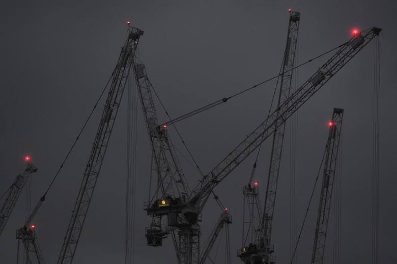 Construction cranes are seen at dusk on a grey day in London, Britain, January 9, 2017. REUTERS/Toby Melville