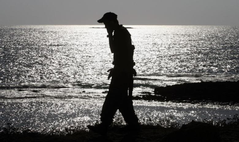 An Israeli soldier speaks on a mobile phone with his mother while walking alongside a beach near the city of Nahariya August 15, 2006. REUTERS/Petr Josek