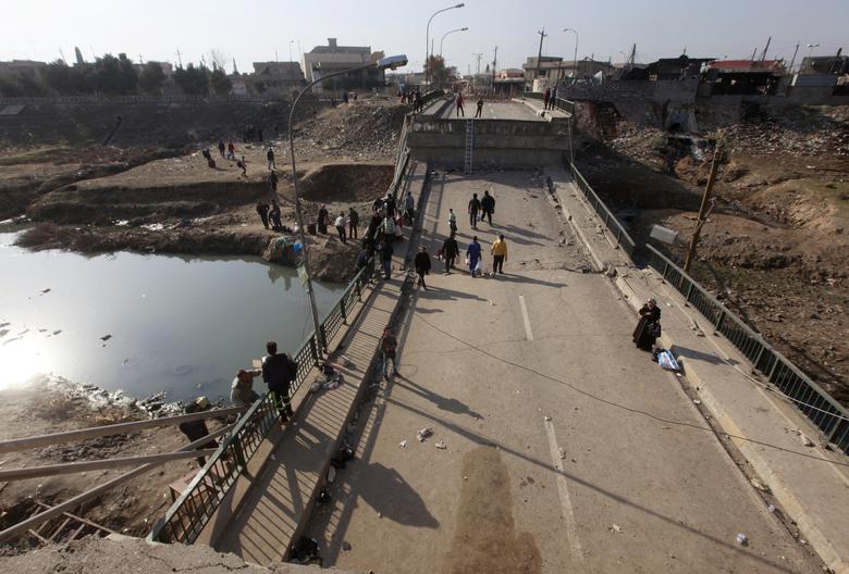 Displaced people, who fled Islamic State militants, cross the bridge in Al-Muthanna neighborhood of Mosul, Iraq, January 9, 2017. Picture taken January 9, 2017. REUTERS/Alaa Al-Marjani
