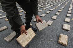 Un polícia colombiano muestra los paquetes de cocaina confiscados en Cali, Colombia. 15 de abril 2013. Las Fuerzas Armadas de Colombia confiscaron una cifra récord de 378,3 toneladas de cocaína en el 2016, un 49 por ciento más que en el año previo, por una mejor coordinación en las actividades de inteligencia y mayores decomisos, informó el miércoles el Ministro de Defensa, Luis Carlos Villegas. REUTERS/Stringer