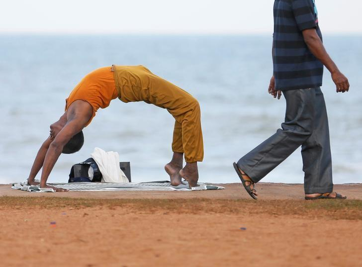 A man performs yoga as another man walks past him at Galle Face Green in Colombo, Sri Lanka July 6, 2016. REUTERS/Dinuka Liyanawatte