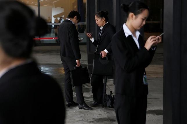1月12日、中国国家発展改革委員会(NDRC)は、2016─18年に情報インフラの整備に1兆2000億元(約1735億7000万ドル)を投じると発表した。写真は携帯電話をチェックする人々。浙江省で昨年11月撮影(2017年 ロイター/Aly Song)
