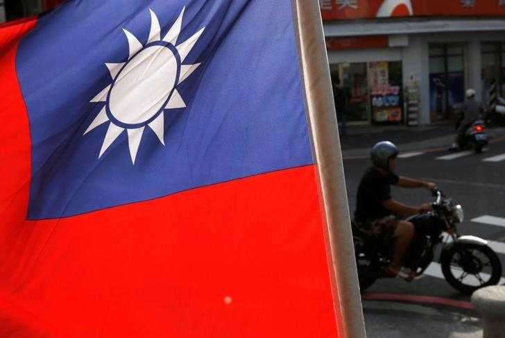 Motorcyclists ride past a Taiwanese national flag on referendum day that will decide if casinos can be built on the outlying island of Penghu, Taiwan October 15, 2016. REUTERS/Tyrone Siu/File Photo