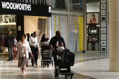 Shoppers leave a Woolworths store at a shopping centre in Lenasia, south of Johannesburg, August 28, 2013.    REUTERS/Siphiwe Sibeko