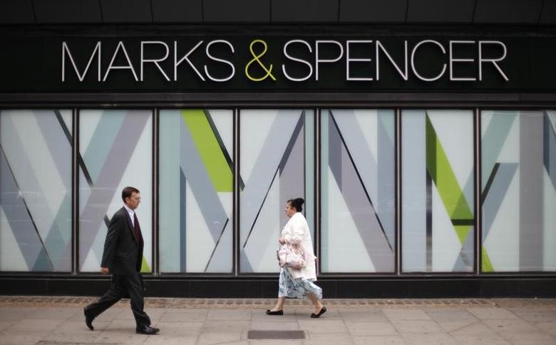Pedestrians walk past a branch of Marks & Spencer in northwest London, Britain July 8, 2014. REUTERS/Suzanne Plunkett/File Photo