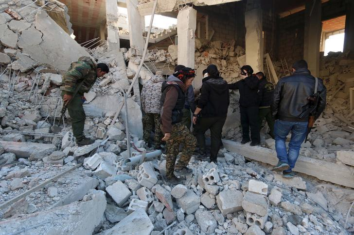 Kurdish fighters from the People's Protection Units (YPG) inspect damage at a site hit by one of the three truck bombs, in the YPG-controlled town of Tel Tamer, Syria December 11, 2015.  A spokesman for the Syrian Kurdish YPG militia said the death toll from a triple truck bomb attack in a town in northeastern Syria on Friday had risen to 50 to 60 people, with more than 80 others wounded. One of the blasts occurred outside a hospital, another at a market and the third in a residential area in the YPG-controlled town of Tel Tamer, Redur Xelil said via Internet messaging service.   REUTERS/Rodi Said