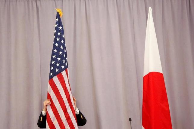 1月12日、トランプ米次期大統領が「国境税」(ボーダータックス)の導入意思をあらためて示し、第2次世界大戦以降の自由貿易体制に陰りが出てきた。写真は安倍首相がトランプ氏との初会談後に行った記者会見の場に飾られた両国の国旗。2016年11月撮影(2017年 ロイター/Andrew Kelly)