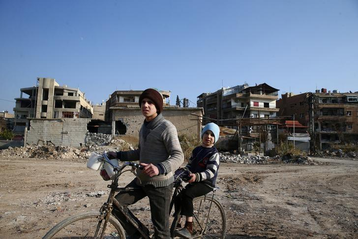 Boys ride a bicycle in the rebel held besieged city of Douma, in the eastern Damascus suburb of Ghouta, Syria January 7, 2017. REUTERS/Bassam Khabieh/Files