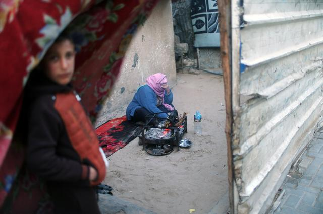 A Palestinian woman warms herself by a fire during a power cut at her house in Beit Lahiya in the northern Gaza Strip January 11, 2017. Picture taken January 11, 2017. REUTERS/Mohammed Salem