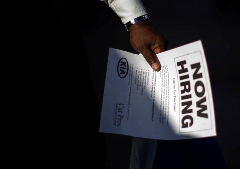 A man holds a leaflet at a military veterans' job fair in Carson, California October 3, 2014.   REUTERS/Lucy Nicholson/File Photo