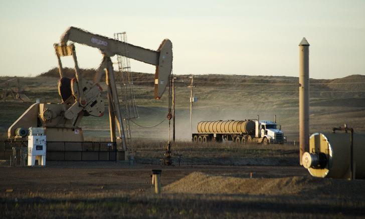 A service truck drives past an oil well on the Fort Berthold Indian Reservation in North Dakota, November 1, 2014.  REUTERS/Andrew Cullen