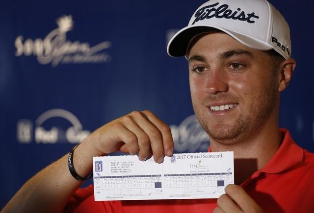 Jan 12, 2017; Honolulu, HI, USA; PGA golfer Justin Thomas holds up his official scorecard after shooting a 59 during the first round of the Sony Open golf tournament at Waialae Country Club. Mandatory Credit: Brian Spurlock-USA TODAY Sports